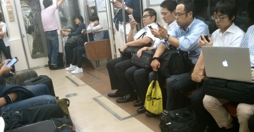 People using their mobile phone in the metro to kill time.